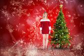 Zusammengesetztes Bild von hübschen Mädchen lächelnd im Santa-outfit — Stockfoto
