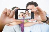 Smiling young family looking at camera — Stock Photo