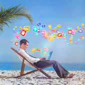 Businessman with laptop on beach — Stock Photo