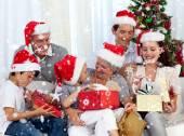 家族の家にクリスマス プレゼントを開ける — ストック写真