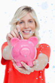 Piggy bank getting dollar notes from a young woman — Stock Photo
