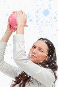 Brunette woman holding an empty piggy bank — Stock Photo