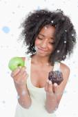 Young woman hardly hesitating between a muffin — Stockfoto