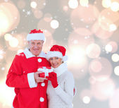 Festive mature couple holding gift — Stock Photo