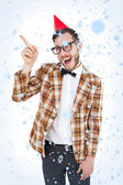 Composite image of geeky hipster in party hat pointing — Stock Photo