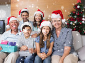 Family in christmas hats with gift boxes — Stockfoto