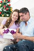 Loving couple opening christmas gift — Foto de Stock