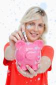Woman putting notes into a pink piggy bank — Photo
