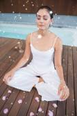 Peaceful brunette in white sitting in lotus pose — Foto Stock