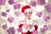 Composite image of pretty girl in santa costume holding gift box — Stock Photo