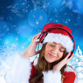Sexy santa girl listening to music — Stockfoto