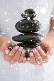 Beauty therapist holding pile of stones — Stock Photo