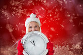 Happy festive blonde with clock — Стоковое фото