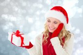 Composite image of happy festive blonde with gift — Stock Photo