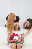 Cheerful young women surprising friend — Stock fotografie