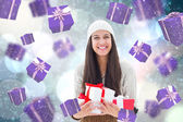 Composite image of festive brunette holding gifts — Foto Stock