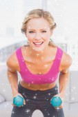 Fit blonde lifting dumbbells and smiling — Stockfoto