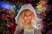 Composite image of sexy santa girl opening gift — Stock Photo