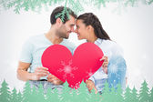 Cute couple sitting holding red heart — Stock Photo