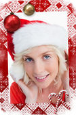 Young blonde woman putting on the santa claus — Stock Photo