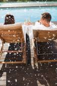 Couple toasting champagne by swimming pool — Foto de Stock