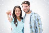 Happy young couple showing new house key — Stock Photo