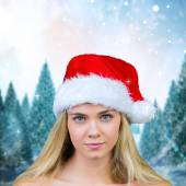 Composite image of blonde with bare shoulders in santa hat — Stock Photo
