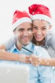 Couple in santa hats shopping online — 图库照片