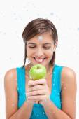Smiling teenager looking at a green apple — Stock Photo