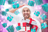 Composite image of festive man holding christmas gifts — Stock fotografie