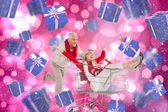 Composite image of happy festive couple messing in trolley — Stock Photo