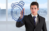 Businessman standing and pointing to clock — Stockfoto