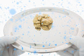 Composite image of golden nuggets on a silver tray — ストック写真