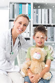Friendly doctor with boy holding teddy bear — Stock Photo