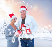 Mature couple holding christmas gifts — Stock Photo