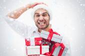 Stressed festive man holding gifts — Stock Photo