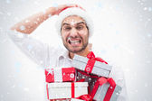 Stressed festive man holding gifts — Stockfoto