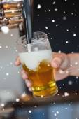 Hand holding glass filling beer — Stock Photo