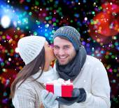 Winter couple holding gift — Stockfoto