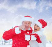 Festive mature couple holding gift — Stock Photo