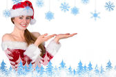 Pretty redhead in santa outfit presenting with hands — Stock Photo