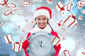 Composite image of festive brunette holding clock — Stockfoto