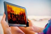 Woman sitting on beach using tablet — Stock Photo
