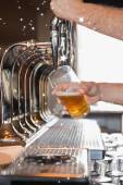 Composite image of bartender pulling a pint of beer — Stock Photo