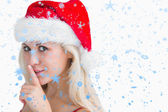 Composite image of woman in santa hat making silence gesture — Stock Photo
