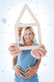 Happy couple holding house outline — Stock Photo