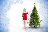 Composite image of pretty girl presenting in santa outfit — Stock Photo