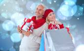 Festive couple with gifts and bags — Stockfoto