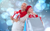 Festive couple with gifts and bags — Stock Photo