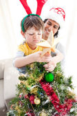Father and son decorating Christmas tree — Stock Photo